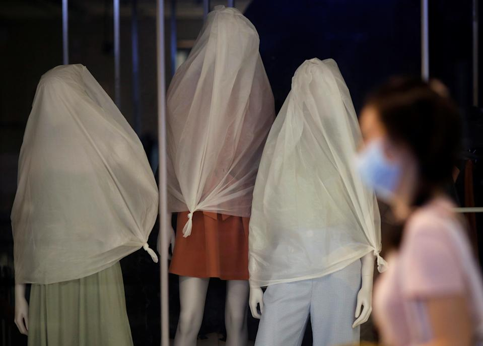A woman wearing a protective face mask passes covered mannequins as shops remain closed amid the outbreak here on 15 May, 2020. (PHOTO: Reuters)