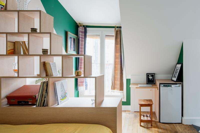 "The library around the bed was designed as a ""book nest,"" where geometric modules create a separation between the bed and the large, main window."