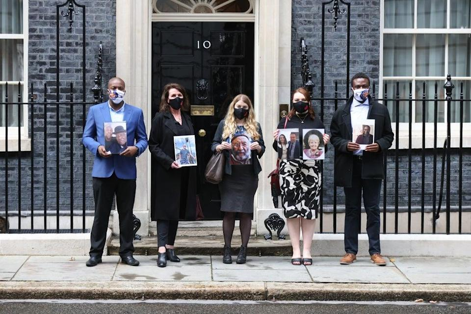 Members of the Covid-19 Bereaved Families for Justice group holding photos of loved ones outside 10 Downing Street, London, after their private meeting with Boris Johnson (James Manning/PA) (PA Wire)