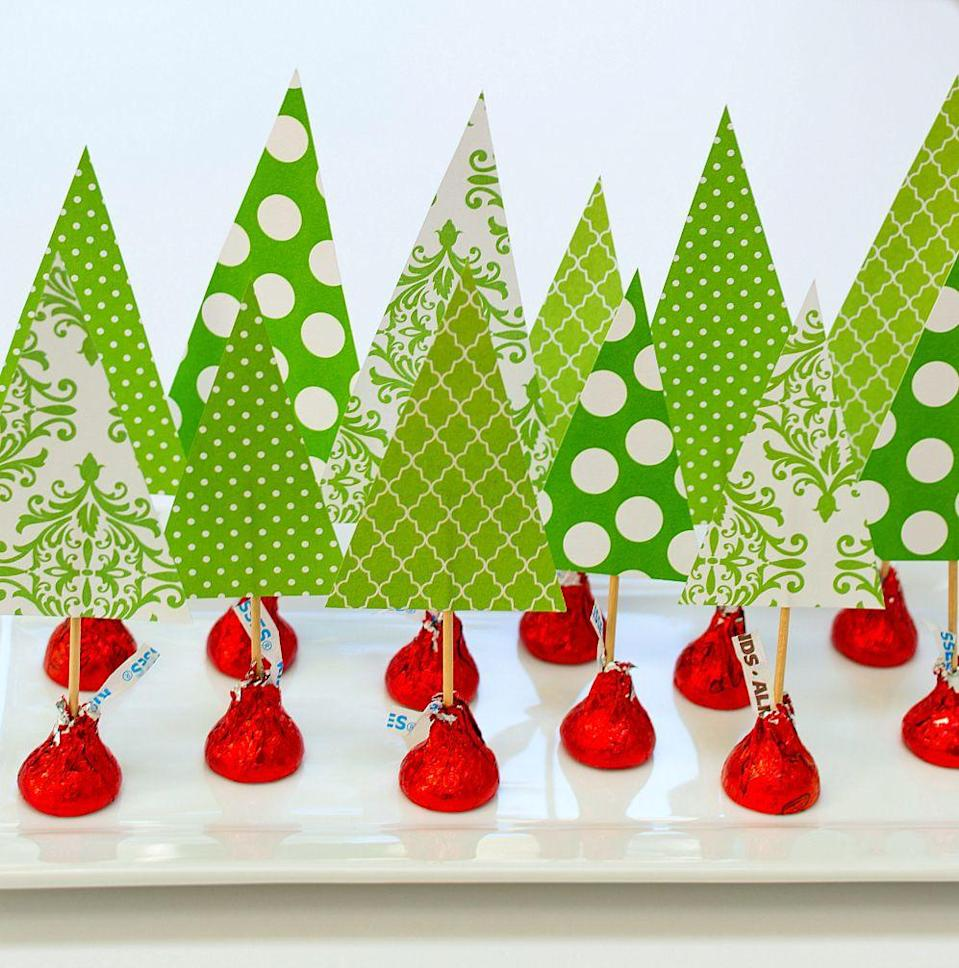 """<p>Use Hershey Kisses wrapped in holiday-color foils to make this ultra-easy project: Cut triangles from scrapbooking paper to represent trees, and let kids poke them into the top of the Kisses with toothpicks. Arrange them on a platter for a table centerpiece that's homemade, affordable… and delicious, too.</p><p><em><a href=""""https://www.itallstartedwithpaint.com/christmas-crafts-with-kids-kisses/"""" rel=""""nofollow noopener"""" target=""""_blank"""" data-ylk=""""slk:Get the tutorial at It All Started With Paint"""" class=""""link rapid-noclick-resp"""">Get the tutorial at It All Started With Paint </a></em></p>"""