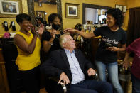 Democratic gubernatorial candidate, former Gov. Terry McAuliffe, seated, seeks hair style advice from Karin Harris, right, her daughter Nicole Harris, left, as well as Caroline Mayfield in Karen's House of Beauty in downtown Petersburg, Va., Saturday, May 29, 2021. McAuliffe faces four other Democrats in the a primary June 8. (AP Photo/Steve Helber)