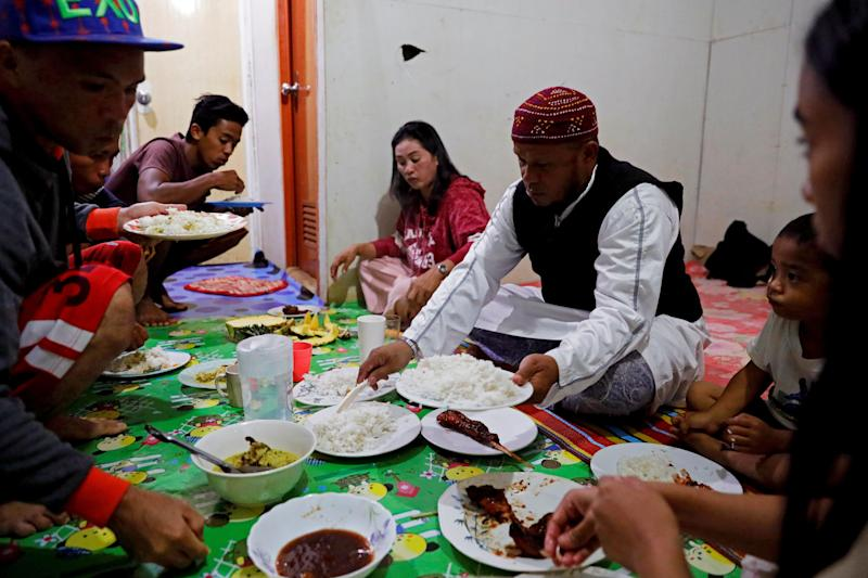 Mohammad Ali Acampong, 42, and his family break their fast with rice, chicken and pineapples during Ramadan in their temporary shelter in Marawi City, Lanao del Sur province, Philippines. (Photo: Eloisa Lopez/Reuters)