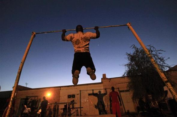 A member of the national weightlifting team trains as he prepares to compete with other athletes for the selection of the Olympics team in Khartoum, Sudan, February 28, 2012.