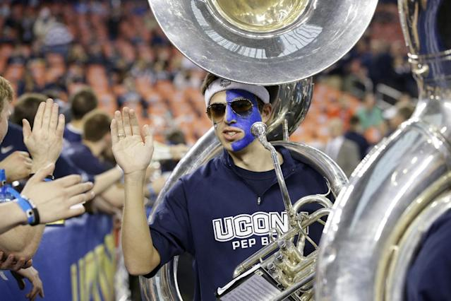 A Connecticut band member cheers before the NCAA Final Four tournament college basketball championship game against Kentucky, Monday, April 7, 2014, in Arlington, Texas. (AP Photo/Tony Gutierrez)