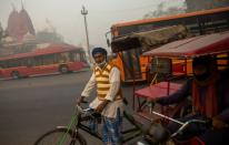 A rickshaw puller waits for customers on a smoggy morning in the old quarters of Delhi