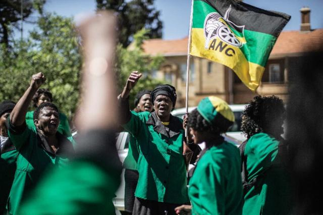 Members of the women's league of the South African ruling party, the African National Congress, sing and dance in protest against Oscar Pistorius outside the appeals court in Bloemfontein on November 3, 2015 (AFP Photo/Gianluigi Guercia)