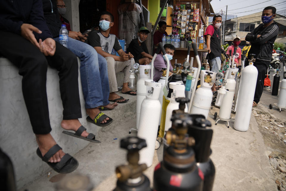 In this July 5, 2021, file photo, people queue up to refill their oxygen tanks at a filling station in Jakarta, Indonesia. Images of bodies burning in open-air pyres during the peak of the pandemic in India horrified the world in May, but in the last two weeks Indonesia and two other Southeast Asian nations have surpassed India's peak per capita death rate as a new coronavirus wave tightens its grip on the region. (AP Photo/Dita Alangkara, File)