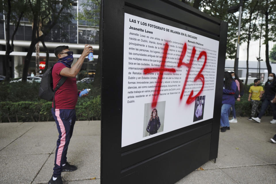 A demonstrator protesting the disappearance of 43 university students sprays graffiti on a display during a march on the seventh anniversary of their disappearance, in Mexico City, Sunday, Sept. 26, 2021. Relatives continue to demand justice for the Ayotzinapa students who were allegedly taken from the buses by the local police and handed over to a gang of drug traffickers. (AP Photo/Marco Ugarte)