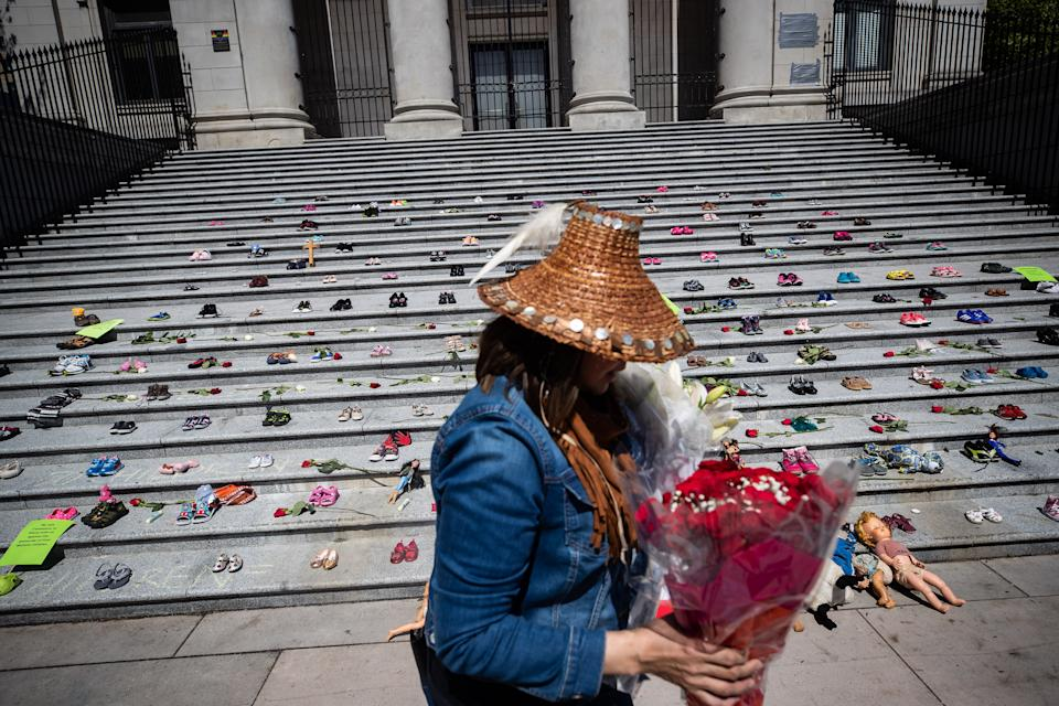 <p>A woman carries flowers to be placed with 215 pairs of children's shoes on the steps of the Vancouver Art Gallery as a memorial to the 215 children whose remains have been found buried at the site of a former residential school in Kamloops, in Vancouver, on Friday, May 28, 2021. Chief Rosanne Casimir of the Tk'emlups te Secwépemc First Nation First Nation said in a news release Thursday that the remains were confirmed last weekend with the help of a ground-penetrating radar specialist. THE CANADIAN PRESS/Darryl Dyck</p>