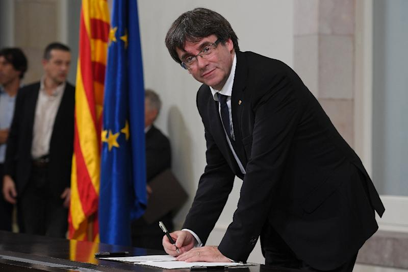 Catalan regional government president Carles Puigdemont signs a document about the independence of Catalonia at the Catalan regional parliament in Barcelona on October 10, 2017 (AFP Photo/LLUIS GENE)