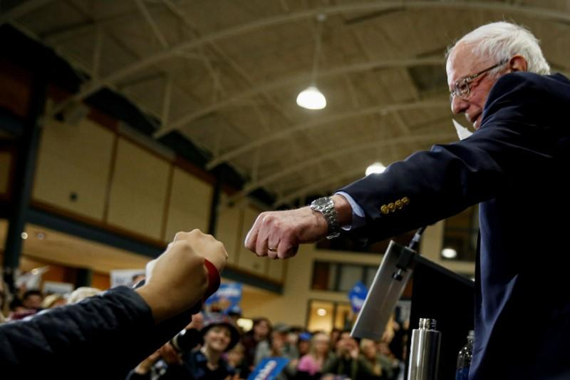 FILE PHOTO: Democratic U.S. presidential candidate Senator Bernie Sanders gives a fist bump to people in the audience at the end of a campaign town hall event in Exeter