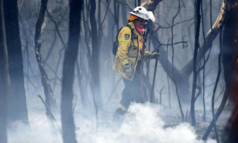 A firefighter mops up at South Turramurra