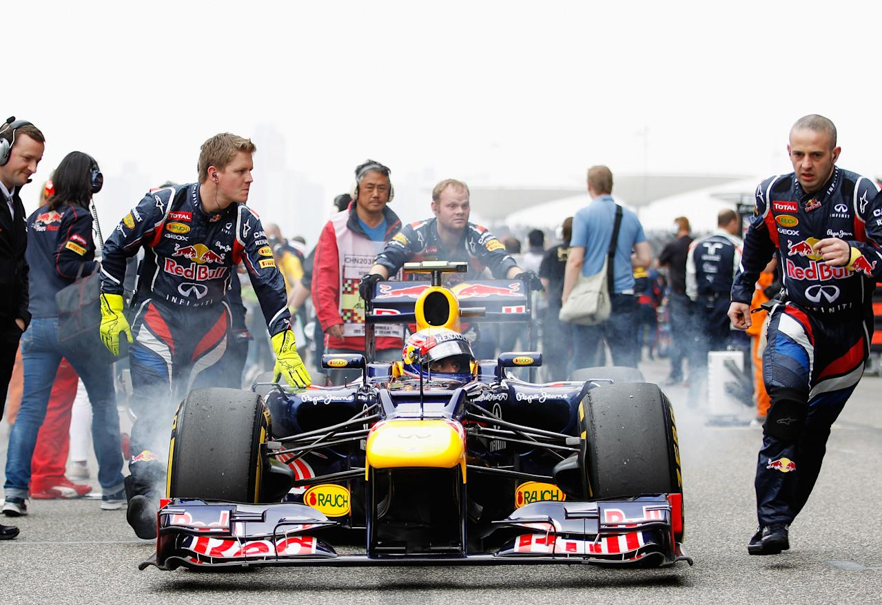 SHANGHAI, CHINA - APRIL 15:  Mark Webber of Australia and Red Bull Racing arrives on the grid before the Chinese Formula One Grand Prix at the Shanghai International Circuit on April 15, 2012 in Shanghai, China.  (Photo by Paul Gilham/Getty Images)