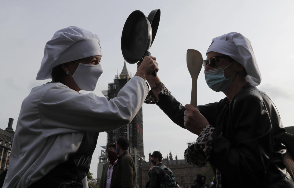 Hospitality workers beat their pans to protest in Parliament Square in London, Monday, Oct. 19, 2020. Hospitality workers are demonstrating outside Parliament against tougher coronavirus restrictions and the amount of financial support given by the government to the industry.(AP Photo/Frank Augstein)