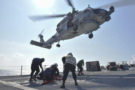 U.S. Navy Sailors participate in a medical training exercise on the deck of the Arleigh Burke-class guided missile destroyer USS Lassen with an MH-60R Seahawk helicopter, in the South China Sea
