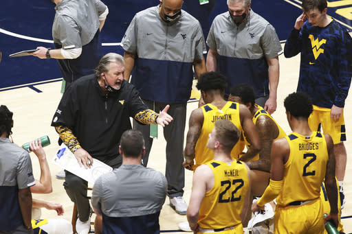 West Virginia coach Bob Huggins speaks with players during the second half of an NCAA college basketball game against Texas Tech Monday, Jan. 25, 2021, in Morgantown, W.Va. (AP Photo/Kathleen Batten)