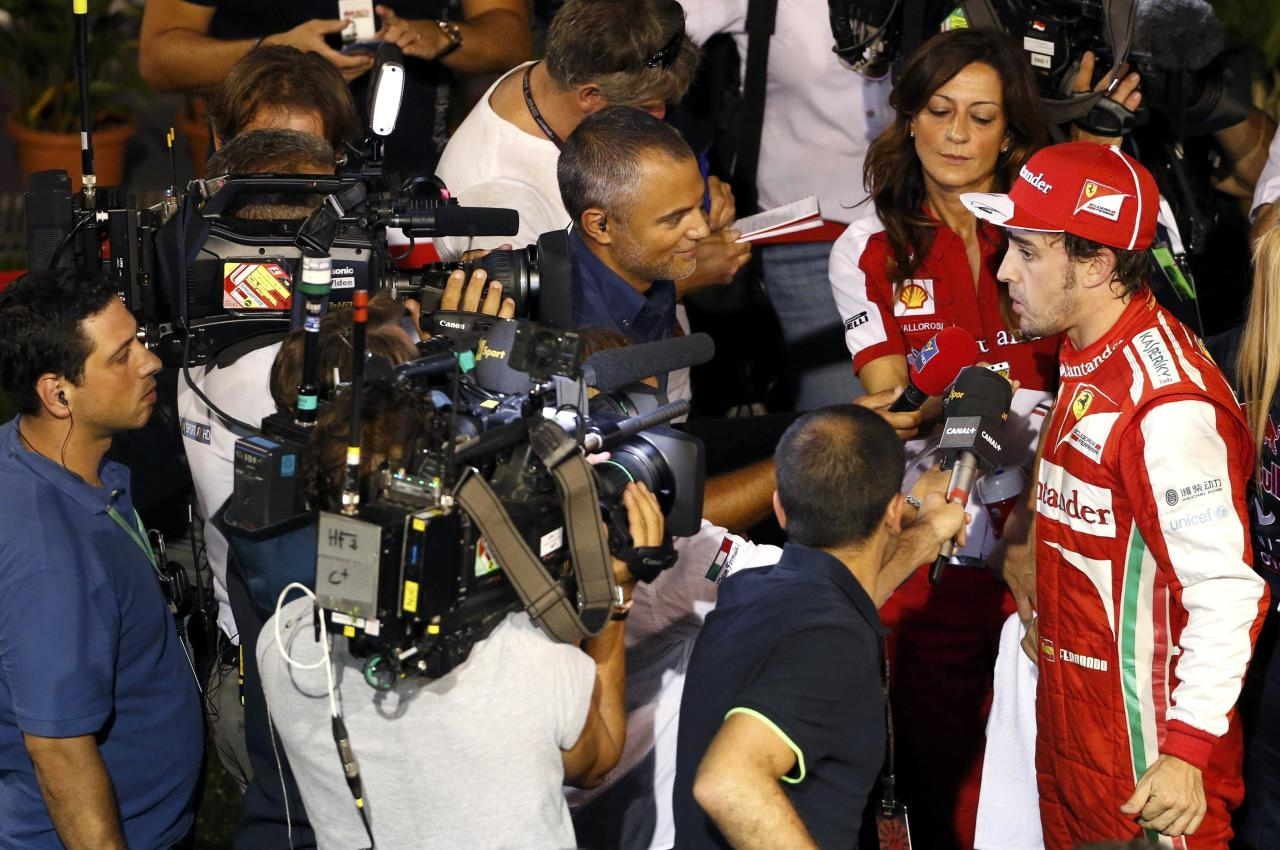 Ferrari Formula One driver Fernando Alonso of Spain is interviewed after the qualifying session of the Singapore F1 Grand Prix at the Marina Bay street circuit in Singapore September 21, 2013. REUTERS/Tim Chong (SINGAPORE - Tags: SPORT MOTORSPORT F1)