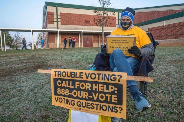 PHOTO: A volunteer with Democracy North Carolina sits to answer questions at Waddell Language Academy in Charlotte, N.C. shortly after the polls opened on election day, Nov. 3, 2020. (Grant Baldwin/AFP via Getty Images)