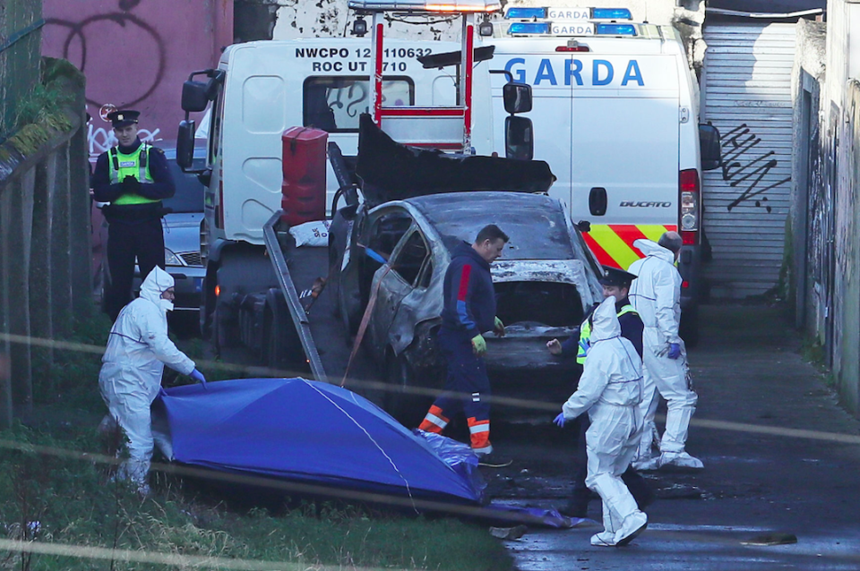 The burnt out car which contained human remains is removed from the scene on Trinity Terrace (PA)
