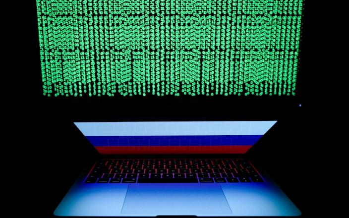 Russian flag is seen on the laptop screen in front of a computer screen on which cyber code is displayed