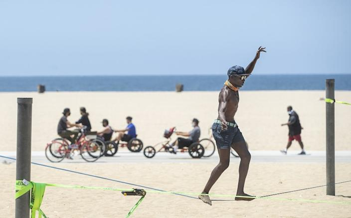 """Jacob Laiser, 38, of Venice balances on a slack line while working out at Santa Monica Beach on Monday. Los Angeles County beaches will close for the July 4 holiday weekend. <span class=""""copyright"""">(Mel Melcon / Los Angeles Times)</span>"""