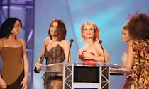 """Ginger Spice gave everyone at the Brits (and everyone watching at home) a huge eyeful in 1997. The bustier part of Geri's red dress slipped down as she and her bandmates stepped up to the podium as she accidentally exposed her right breast. It was a night of daring sartorial choices from the redhead as it was also the year she ensured her place in pop history with <a href=""""https://www.harpersbazaar.com/uk/fashion/fashion-news/news/a40047/story-of-geri-halliwell-union-jack-brits-dress/"""" rel=""""nofollow noopener"""" target=""""_blank"""" data-ylk=""""slk:the iconic Union Jack tea towel dress"""" class=""""link rapid-noclick-resp"""">the iconic Union Jack tea towel dress</a>. (John Ferguson/Mirrorpix/Getty Images)"""
