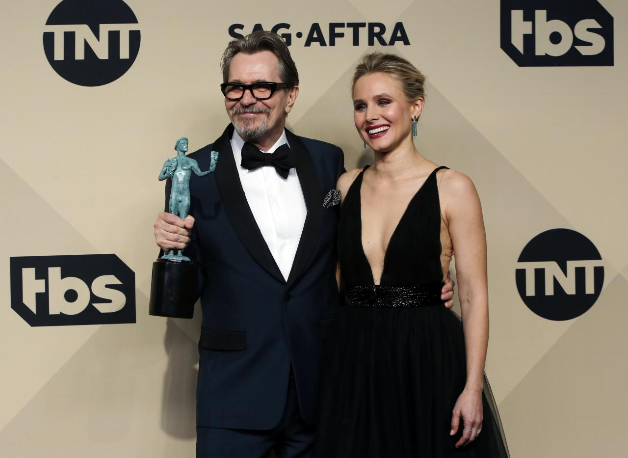 "24th Screen Actors Guild Awards – Photo Room – Los Angeles, California, U.S., 21/01/2018 – Gary Oldman poses backstage with host Kristen Bell as he holds his award for Outstanding Performance by a Male Actor in a Leading Role for ""Darkest Hour"". REUTERS/Monica Almeida"