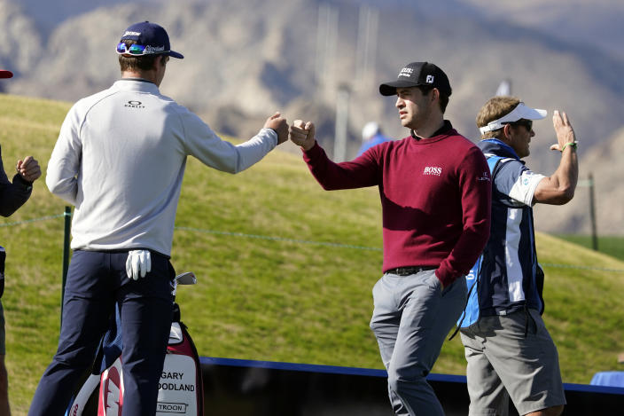 Patrick Cantlay, right, bumps fists with Andrew Putman before teeing off on the first hole during the final round of The American Express golf tournament on the Pete Dye Stadium Course at PGA West, Sunday, Jan. 24, 2021, in La Quinta, Calif. (AP Photo/Marcio Jose Sanchez)