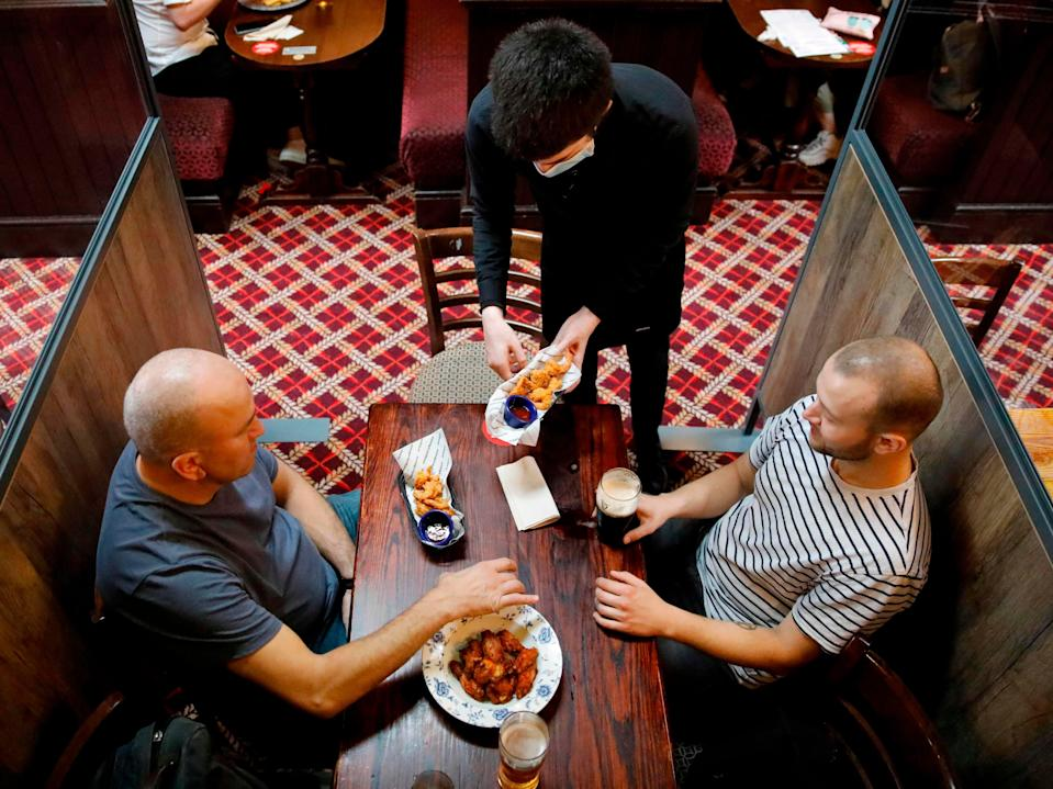 A member of bar staff wearing PPE (personal protective equipment) in the form of a face mask, serves food to seated customers inside the Wetherspoon pub (AFP via Getty Images)