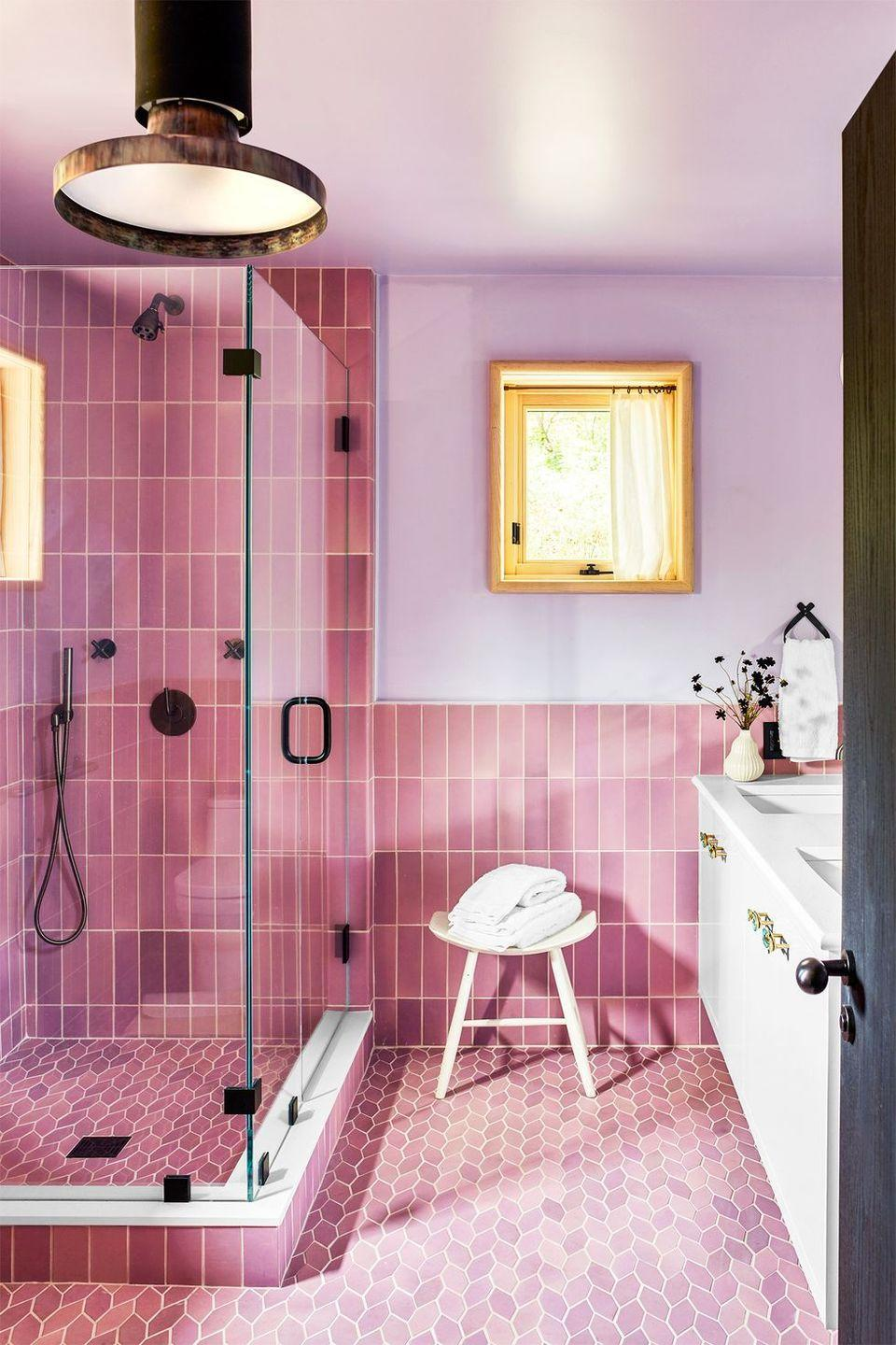 """<p>This bathroom by designer <a href=""""https://coreydamenjenkins.com/"""" rel=""""nofollow noopener"""" target=""""_blank"""" data-ylk=""""slk:Corey Damen Jenkins"""" class=""""link rapid-noclick-resp"""">Corey Damen Jenkins</a> is a lesson in how to have fun with tile and color. The pink subway tiles on the wall and the diamond, almost leaf-like motif on the floors of this bathroom bring in a surge of energy while the lavender paint sets an instant calm . The brass industrial-style fixtures and lighting add just enough contrast and intrigue to the otherwise sweet and romantic space. </p>"""