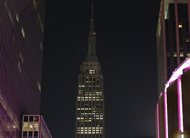 <p>The Empire State Building lights, normally lit in colors, are dimmed Monday, Oct. 2, 2017, in New York, in sympathy for the victims of the mass shooting in Las Vegas. (Photo: Kathy Willens/AP) </p>