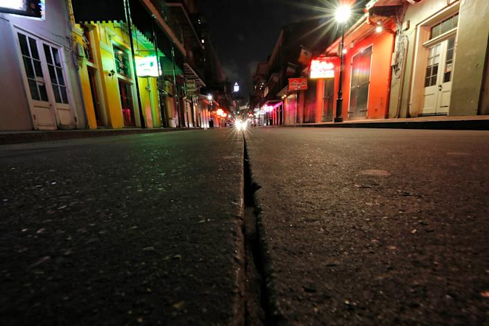 In this Thursday, March 19, 2020, file photo, a view of the nearly deserted scene on Bourbon Street, which is normally bustling with tourists and revelers, in the French Quarter of New Orleans. Like many cities around the country, New Orleans is currently under a shelter-in-place order as it grapples with a growing number of coronavirus cases.