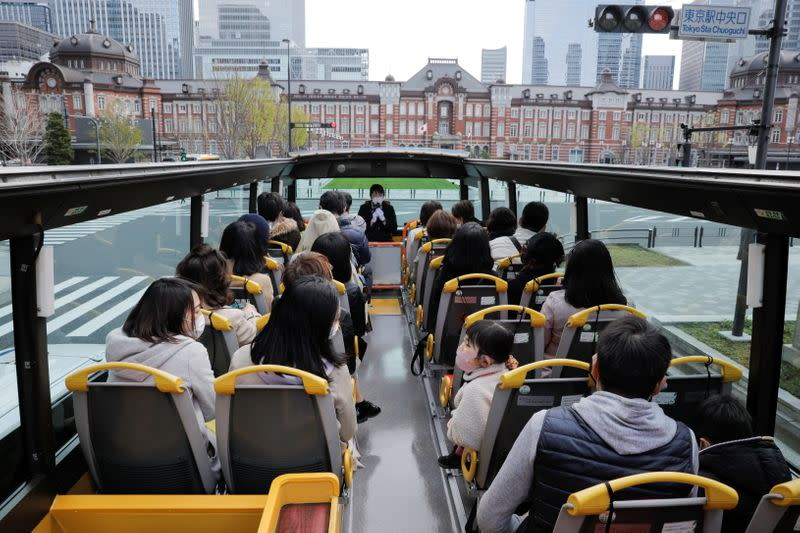 Passengers wearing protective face masks enjoy the viewing of Tokyo Station building from an open-top sightseeing bus, operated by Hato Bus Co., after Japan's government lifted the coronavirus disease (COVID-19) state of emergency in the Tokyo
