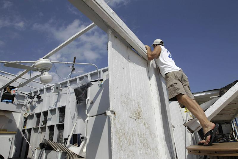 Cabana owner Bill Ryan looks into other roofless cabanas at the Breezy Point Surf Club in the Queens borough of New York, Saturday, Sept. 8, 2012, after a severe weather storm passed through the area. A tornado swept out of the sea and hit the beachfront neighborhood in New York City, hurling debris in the air, knocking out power and startling residents who once thought of twisters as a Midwestern phenomenon. Firefighters were still assessing the damage, but no serious injuries were reported and the area affected by the storm appeared small. (AP Photo/Kathy Willens)