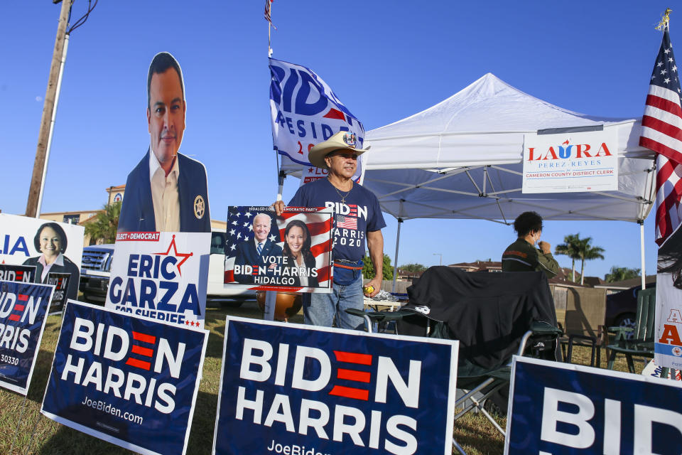 Tito Mata mans his campaign area for presidential candidate Joe Biden and vice presidential candidate Kamala Harris Tuesday, Nov. 3, 2020, outside the polling location at Burns Elementary School in Brownsville, Texas.(Denise Cathey/The Brownsville Herald via AP)
