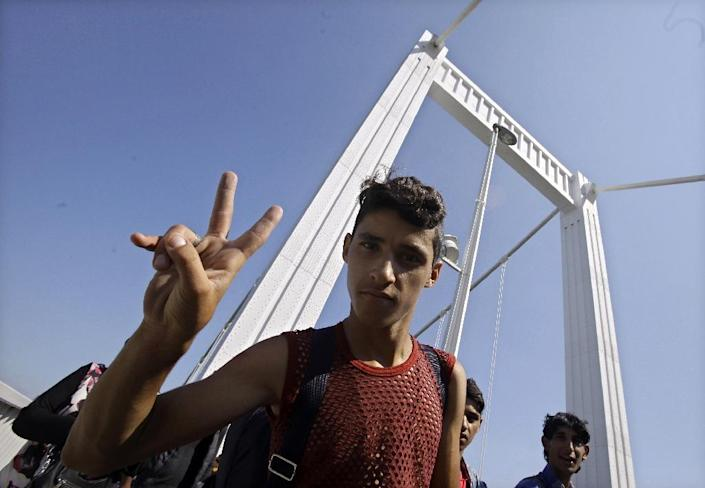 A migrant flashes a V-sign as hundreds of migrants walk across Budapest after leaving the transit zone of the main train station, on September 4, 2015 (AFP Photo/Peter Kohalmi )