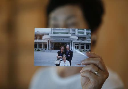Kim Young-ja, a sister of Kim Young-nam who is a South Korean abductee living in North Korea, poses for photographs with a picture showing her abducted brother (R, in picture) taken during a reunion in 2006, during an interview with Reuters in Jeonju July 2, 2014. REUTERS/Kim Hong-Ji