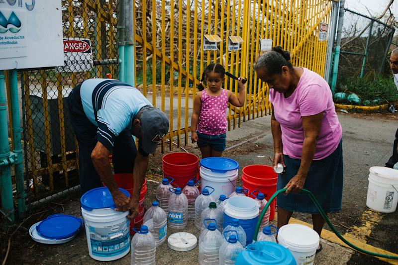 Residents fill containers with water at a center in Rio Grande, Puerto Rico, on Tuesday, Oct. 3, 2017. (Bloomberg via Getty Images)