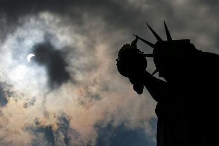 The Monument of Liberty State is photographed while the solar eclipse is seen over Liberty State Island in New York, U.S., August 21, 2017. Location coordinates for this image are 40.4124°N, 74.237°W. REUTERS/Eduardo Munoz
