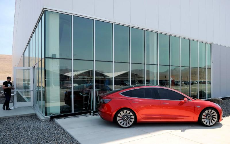 A prototype of the Tesla Model 3 is on display in front of the factory during a media tour of the Tesla Gigafactory which will produce batteries for the electric carmaker in Sparks