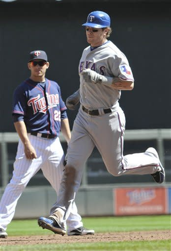 Texas Rangers Josh Hamilton heads for home on his solo home run off Minnesota Twins pitcher Nick Blackburn in the third inning of a baseball game Saturday, April 14, 2012, in Minneapolis. Watching, left, is Twins third baseman Danny Valencia. (AP Photo/Jim Mone)