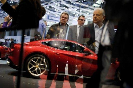 Visitors stand near a Ferrari model car reflected at the Italian car maker's booth at the Geneva Motor Show. Sports cars, reputed for being energy guzzlers, are now trying to boost their green credentials as they seek to attract environmentally conscious consumers and meet new climate standards