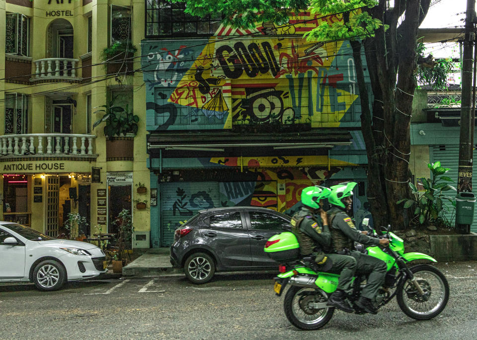 Two police officers in Neon Green drive down the street on their Dirt bike in Medellin Colombia