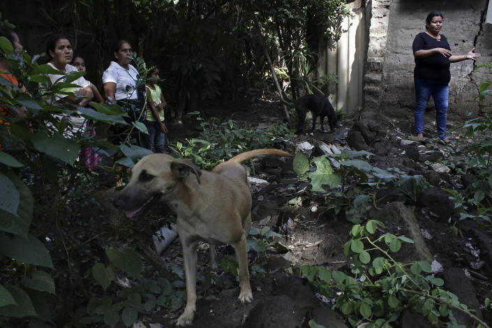 Mudslide survivor Cecilia Flores stands next to her home in Los Angelitos, El Salvador, Wednesday, July 28, 2021. The house has been seriously damaged by government when it cleared land after the October 2020 landslide. (AP Photo/Salvador Melendez)