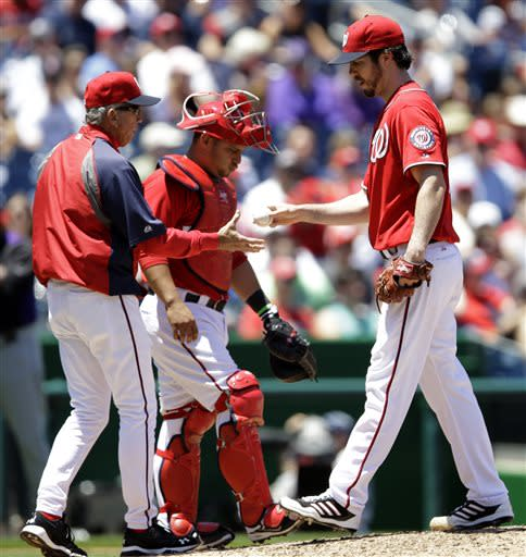 Washington Nationals manager Davey Johnson left, pulls starting pitcher Dan Haren, right, as catcher Jhonatan Solano steps on the mound during the fourth inning of a baseball game against the Colorado Rockies at Nationals Park, Saturday, June 22, 2013, in Washington. (AP Photo/Carolyn Kaster)