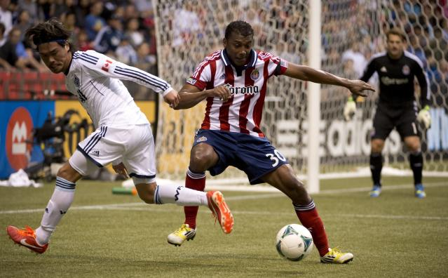 Vancouver Whitecaps FC's Daigo Kobayashi, left, fights for control of the ball with Chivas USA's Oswaldo Minda during the first half of an MLS soccer game in Vancouver, British Columbia, Wednesday, June, 19, 2013. (AP Photo/The Canadian Press, Jonathan Hayward)