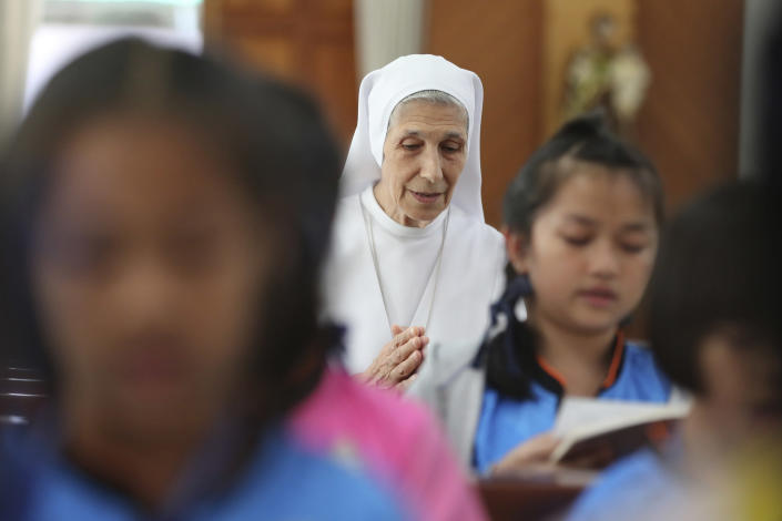 In this Aug. 27, 2019, photo, ST. Mary's School Vice Principal Sister Ana Rosa Sivori, center, and students pray inside a church at the girls' school in Udon Thani, about 570 kilometers (355 miles) northeast of Bangkok, Thailand. Sister Ana Rosa Sivori, originally from Buenos Aires in Argentina, shares a great-grandfather with Jorge Mario Bergoglio, who, six years ago, became Pope Francis. So, she and the pontiff are second cousins. (AP Photo/Sakchai Lalit)