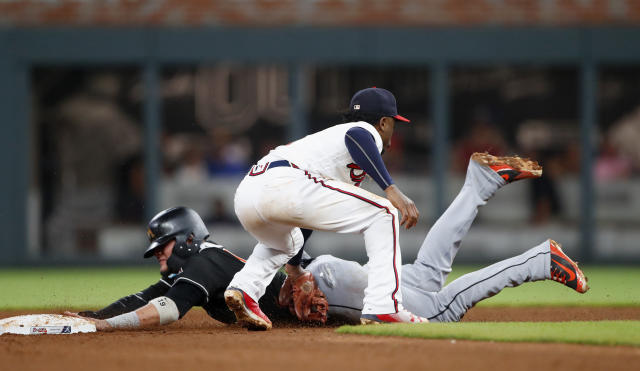 Miami Marlins' Miguel Rojas, left,is tagged out by Atlanta Braves second baseman Ozzie Albies (1) as he tries to steal second base during the fifth inning of a baseball game Friday, May 18, 2018, in Atlanta. (AP Photo/John Bazemore)
