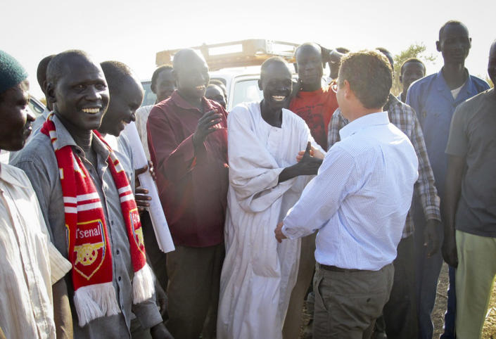 """In this photo taken Tuesday, Dec. 24, 2013 and released by the United Nations Mission in South Sudan (UNMISS) on Wednesday, Dec. 25, 2013, the U.N.'s top humanitarian official in the country Toby Lanzer, center-right, greets people as he makes a visit to assess the humanitarian situation at the U.N. compound where many displaced have sought shelter in Bentiu, in oil-rich Unity state, in South Sudan. In New York, the U.N. Security Council voted unanimously Tuesday to beef up its peacekeeping force in South Sudan and condemned targeted violence against civilians and ethnic communities and called for """"an immediate cessation of hostilities and the immediate opening of a dialogue."""" (AP Photo/UNMISS, Anna Adhikari)"""