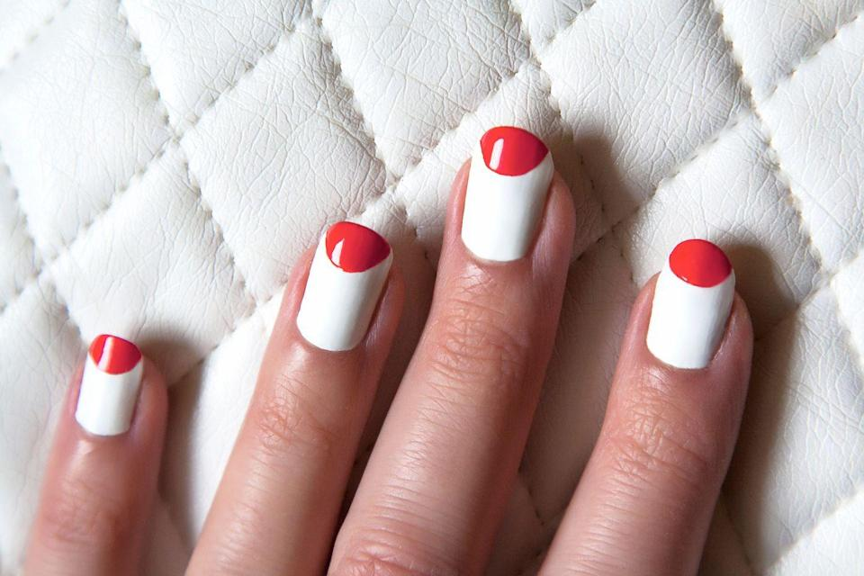 <p>Instead of a traditional French manicure that follows the natural arch of your nail, flip it around to create a half moon. Choose colors like red and white for the holiday.</p>